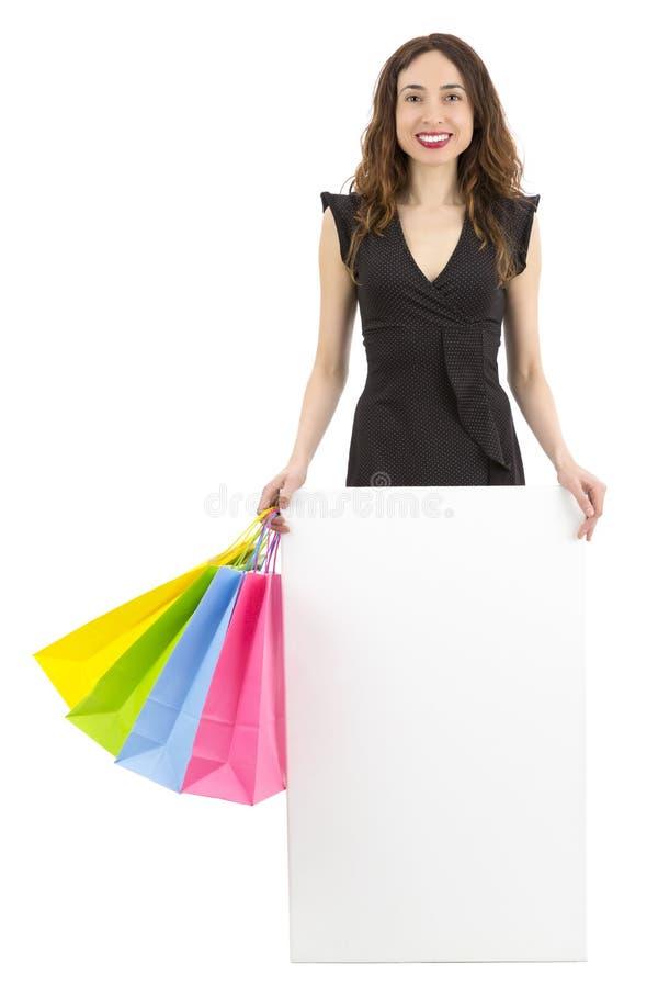 拿着一张空白的海报的购物妇女 库存照片