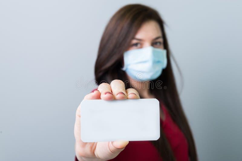 拿着一张空白的白色名片的妇女医生 免版税库存图片