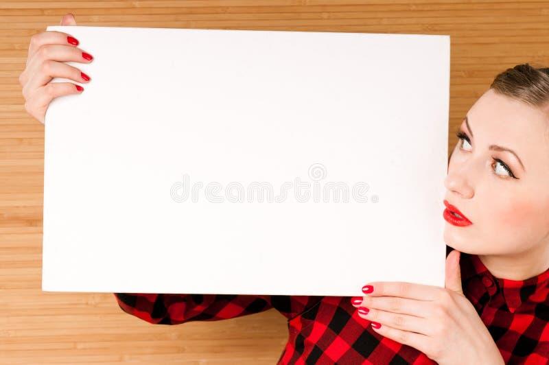 拿着一张空的白色海报的美丽的女孩 免版税库存图片
