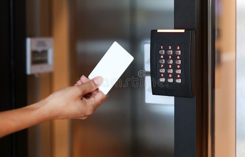拿着一张钥匙卡片的少妇锁和打开门 库存照片