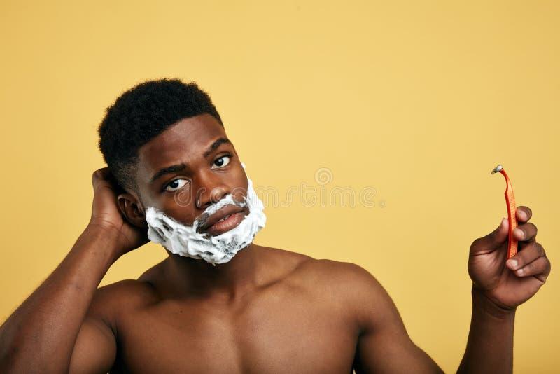 拿着一把一次性剃刀和看照相机的严肃的人 库存照片