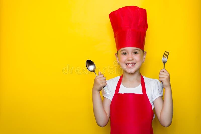 拿着一把匙子和叉子在黄色背景的一位红色厨师的衣服的宽微笑的女孩与拷贝空间 免版税库存照片