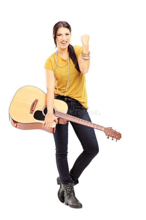 拿着一把声学吉他和打手势幸福的年轻女性 免版税图库摄影