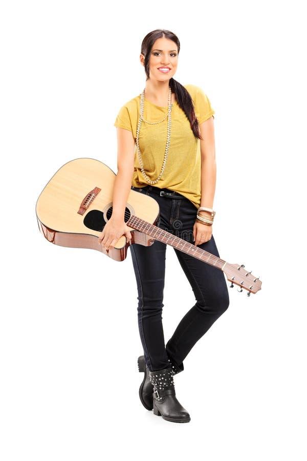 拿着一把声学吉他的女性音乐家 库存图片
