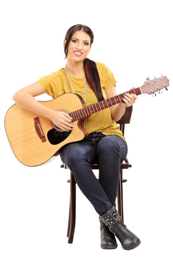 拿着一把声学吉他的椅子的年轻女性音乐家 库存图片