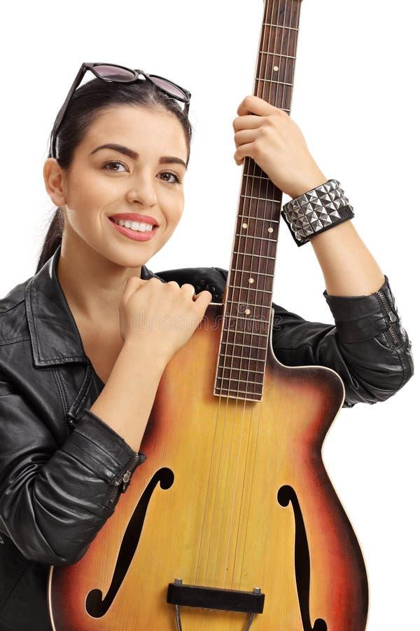拿着一把声学吉他的皮夹克的少妇 免版税库存图片