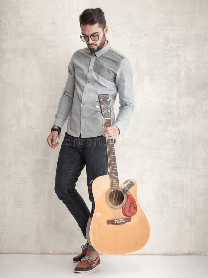拿着一把声学吉他的英俊的人对难看的东西墙壁 免版税库存图片