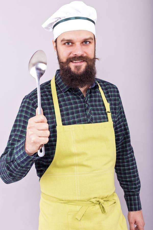 拿着一把大匙子的一位有胡子的厨师的画象 免版税库存图片