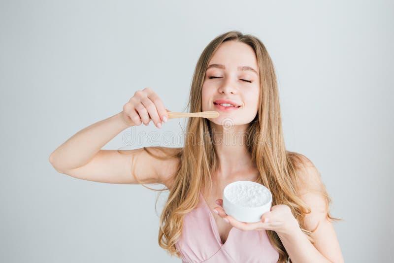 拿着一把有用的竹牙刷和一个瓶子牙粉的女孩 库存照片