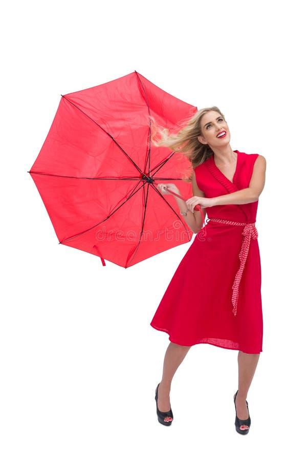 拿着一把残破的伞的俏丽的魅力妇女 免版税库存照片