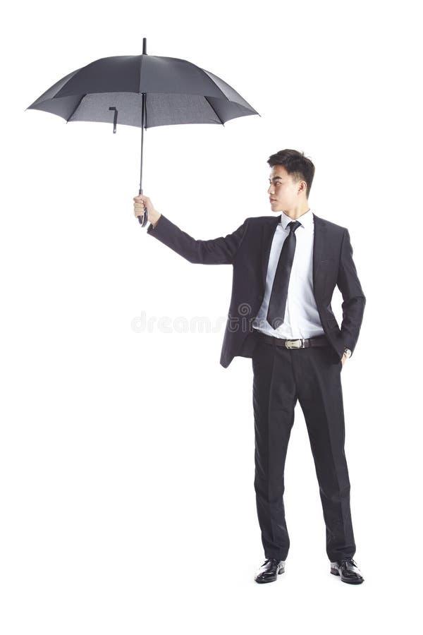 拿着一把黑伞的年轻亚洲商人 免版税库存照片