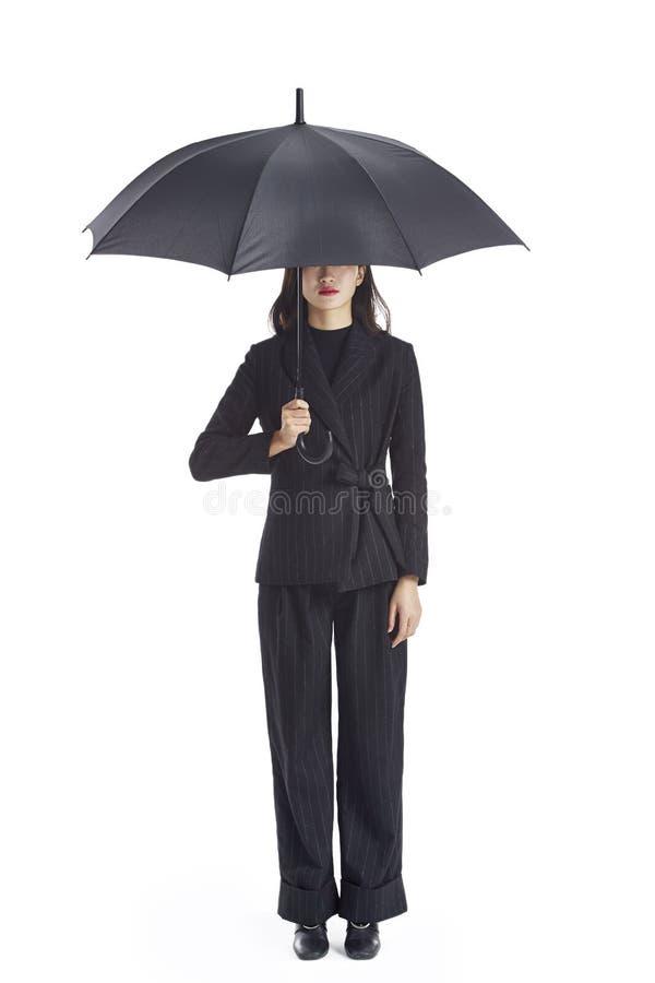 拿着一把黑伞的幼小亚洲企业经营者 图库摄影