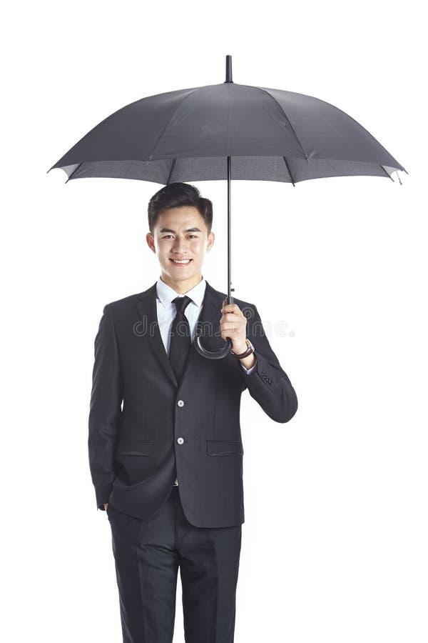 拿着一把黑伞的幼小亚洲企业经营者 免版税库存照片