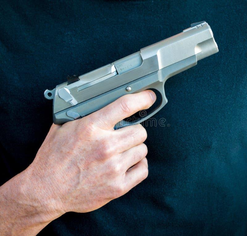 拿着一把9毫米手枪的一只手 库存照片