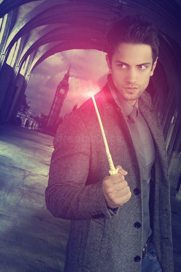 拿着一支不可思议的鞭子的英俊的巫术师 免版税库存图片