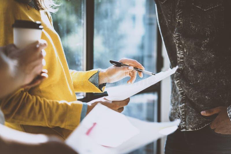 拿着一支笔和纸在她的手上的妇女谈论的与同事 工作在晴朗的工友年轻队  免版税图库摄影