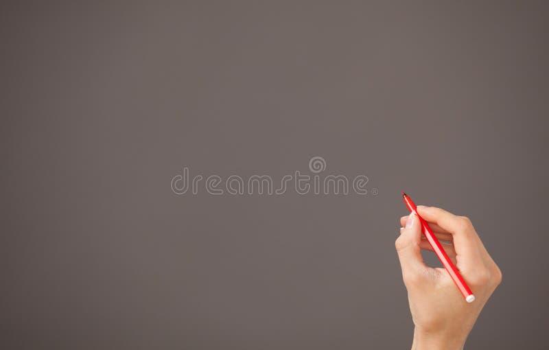 拿着一支红色毡尖的笔的女性手 免版税图库摄影