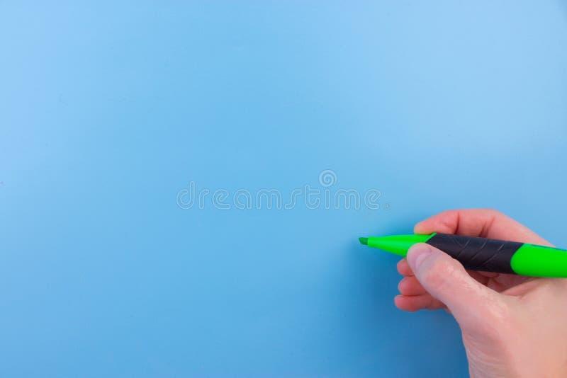 拿着一支绿色铅笔的妇女 免版税库存照片
