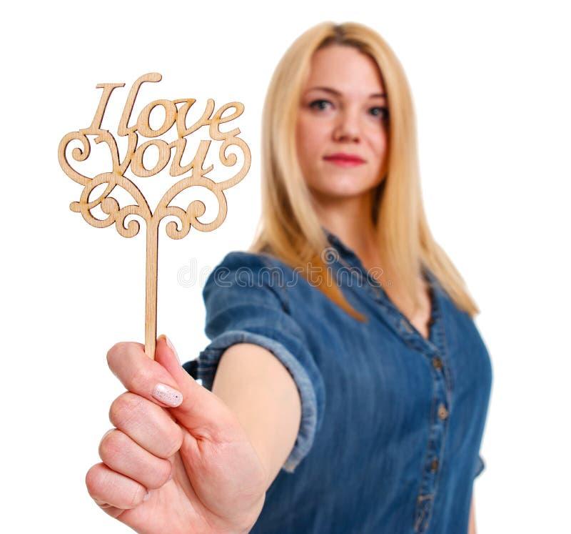 拿着一木标志`我爱你`的浪漫女孩手中 库存照片