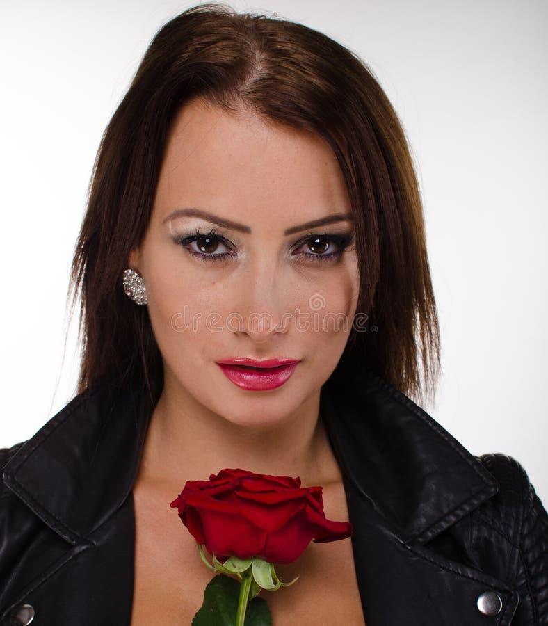 拿着一朵红色玫瑰的惊人的浅黑肤色的男人 库存照片