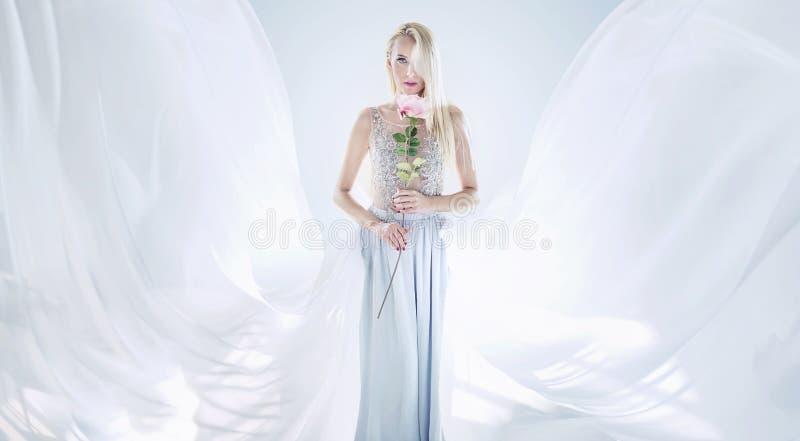 拿着一朵长的玫瑰色花的典雅的白肤金发的妇女 库存图片