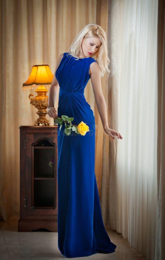 拿着一朵黄色花的长的典雅的蓝色礼服的年轻美丽的豪华妇女。有帷幕的美丽的年轻白肤金发的妇女 免版税库存图片