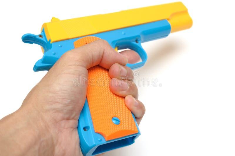 拿着一杆五颜六色的玩具手枪手枪的手 免版税库存图片