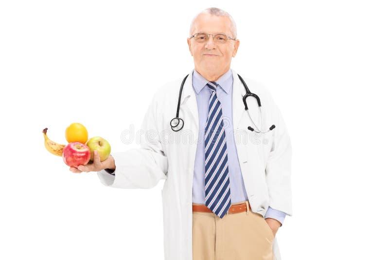 拿着一束果子的成熟医生 免版税库存照片