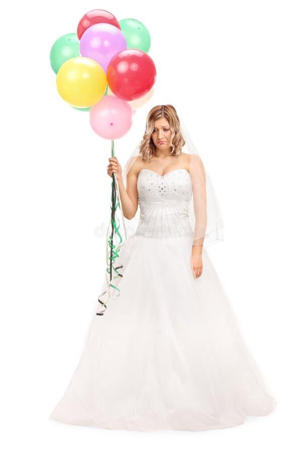 拿着一束气球的哀伤的新娘 免版税库存照片