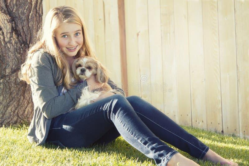 拿着一条小狗的十几岁的女孩 库存照片
