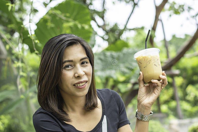 拿着一杯冷的浓咖啡咖啡背景模糊的视图树的亚裔妇女 库存图片