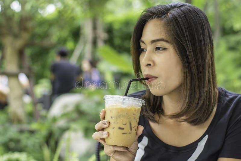 拿着一杯冷的浓咖啡咖啡背景模糊的视图树的亚裔妇女 免版税库存照片