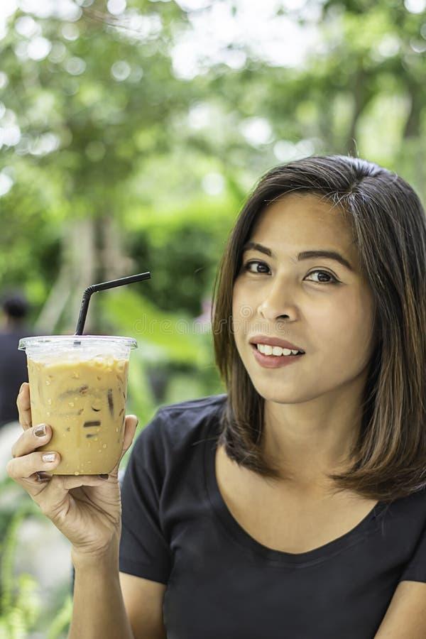 拿着一杯冷的浓咖啡咖啡背景模糊的视图树的亚裔妇女 免版税图库摄影