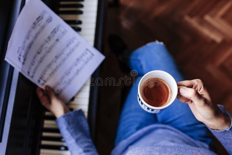 拿着一杯咖啡和弹钢琴的年轻无法认出的妇女通过读音乐纸张 户内音乐概念 顶视图 库存照片