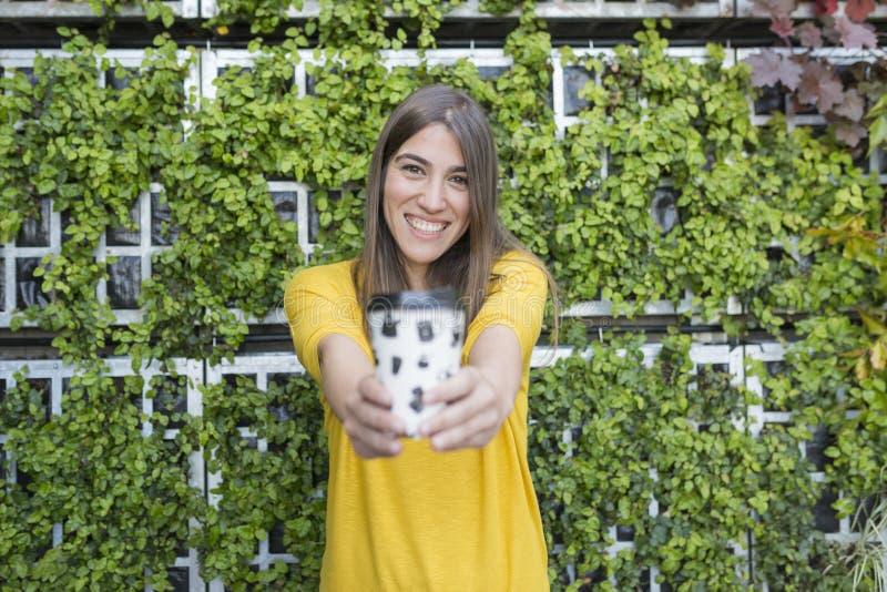 拿着一杯咖啡和微笑的一美丽的年轻女人的画象户外 穿在绿色的一件黄色偶然衬衣 免版税库存图片
