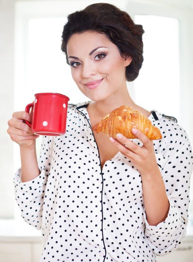 拿着一杯咖啡和新月形面包的愉快的妇女 图库摄影