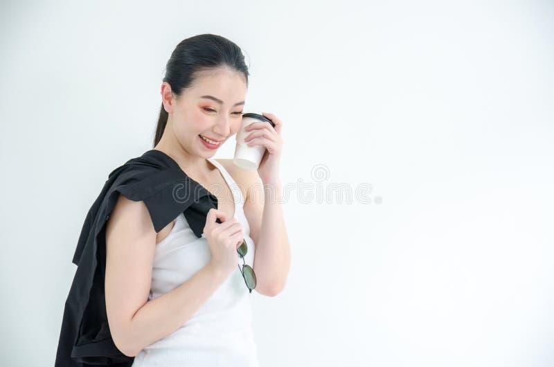 拿着一杯咖啡和黑T恤杉的俏丽的年轻亚裔女商人 在白色背景的被隔绝的演播室画象 库存照片