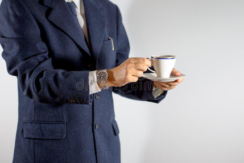 拿着一杯咖啡或茶的典雅的人在手上 免版税库存照片