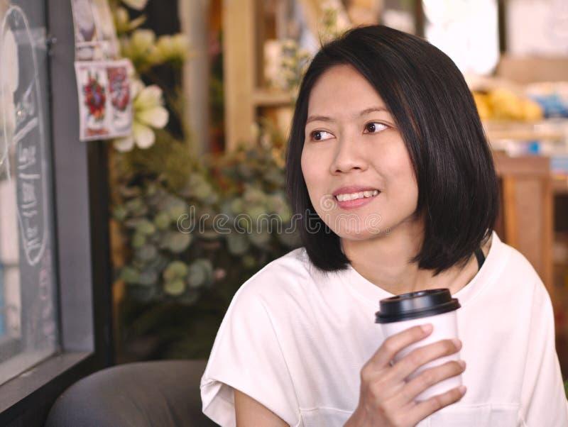 拿着一杯咖啡的亚裔妇女画象看对她的右手在舒适咖啡馆 免版税库存图片