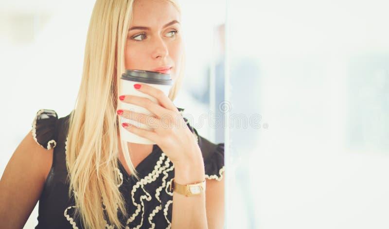 拿着一杯咖啡的女实业家站立在办公室 库存图片