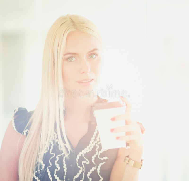 拿着一杯咖啡的女实业家站立在办公室 免版税库存图片