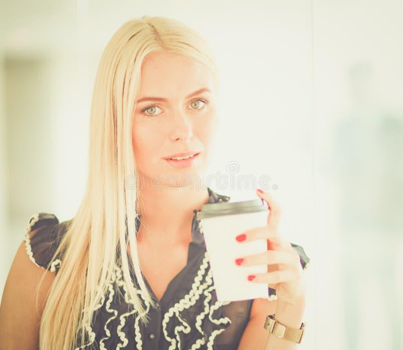拿着一杯咖啡的女实业家站立在办公室 免版税图库摄影