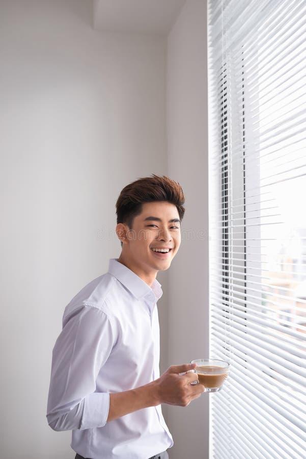 拿着一杯咖啡的年轻商人,当站立在办公室窗口附近时 免版税图库摄影