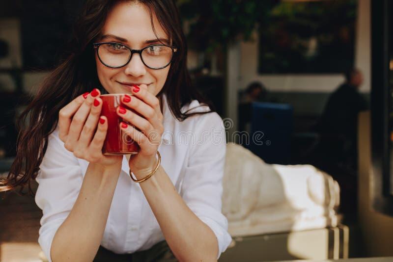 拿着一杯咖啡的美丽的年轻女人在咖啡馆 食用的咖啡馆的女实业家咖啡 免版税库存照片