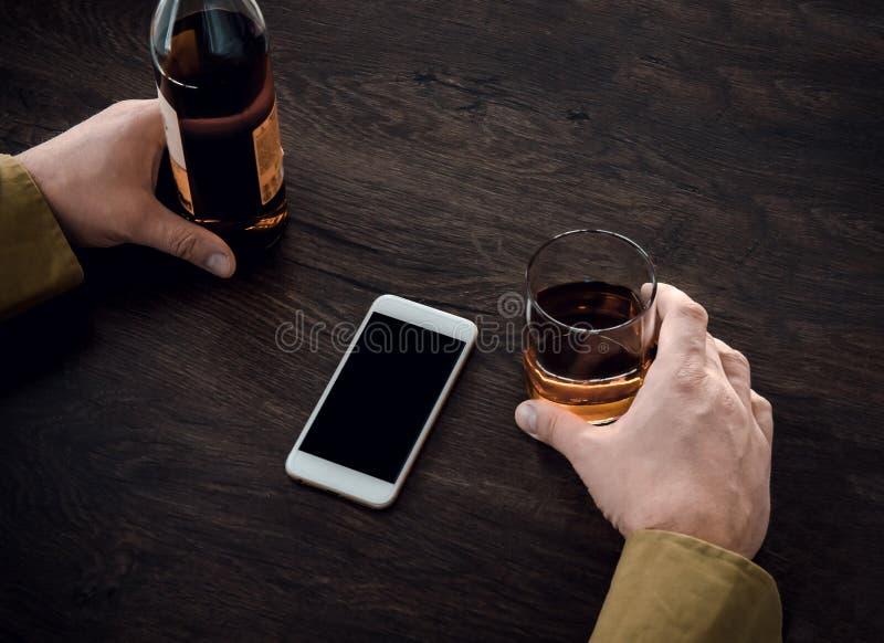拿着一杯威士忌酒和一个瓶的一个人酒精,在桌上是一个手机 库存照片