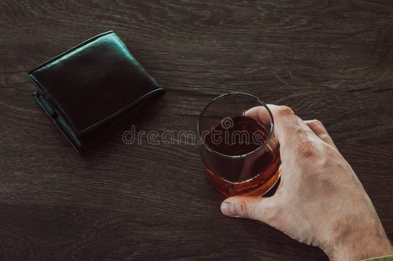 拿着一杯威士忌酒的一个人 r 与酒精的一块玻璃和钱包在桌上 免版税库存图片