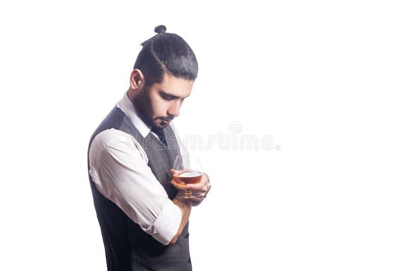 拿着一杯威士忌酒的英俊的有胡子的商人 免版税库存图片