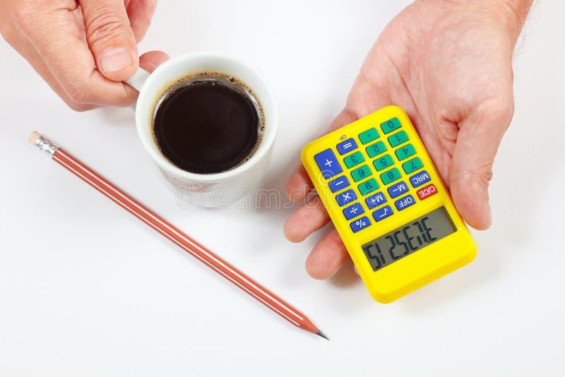 拿着一杯数字式计算器和咖啡在白色背景的手 库存图片