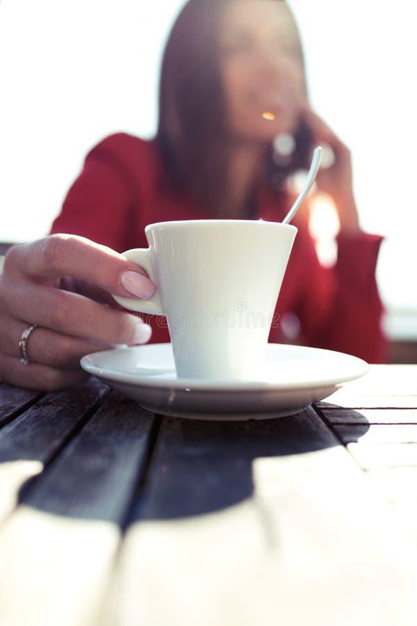 拿着一杯热的咖啡的年轻女人,当谈话与她的坐在coffe商店时大阳台的手机  免版税库存照片
