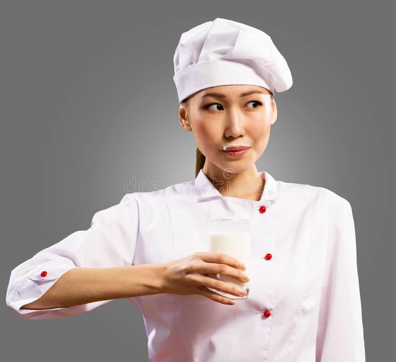 拿着一杯牛奶的女性亚裔主厨 库存照片